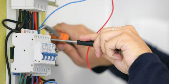 щиток, провода, руки, отвёртка и щипцы в руках