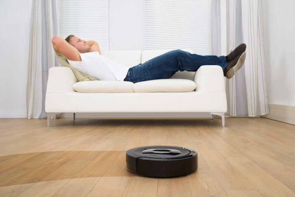 робот-пылесос, мужчина на диване