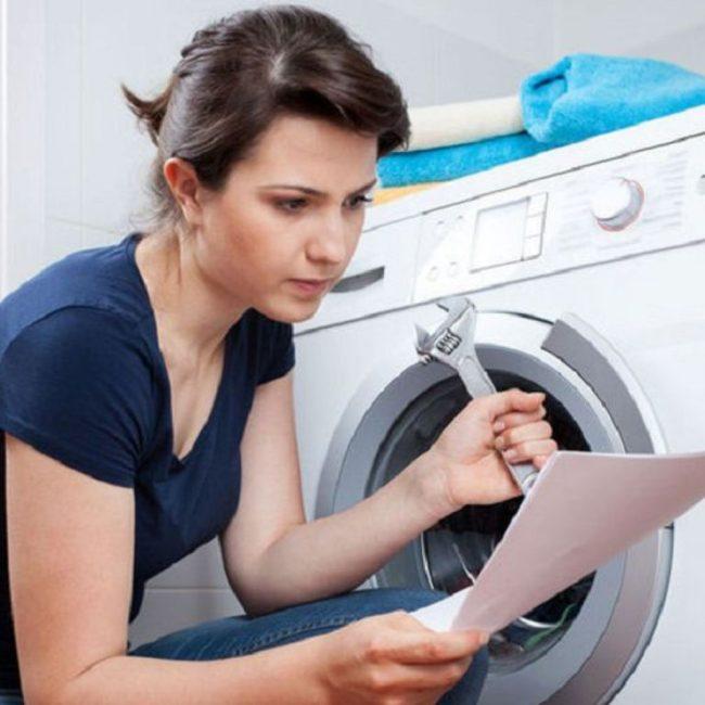 женщина с ключем машины возле стиральной читает инструкцию, блокировка