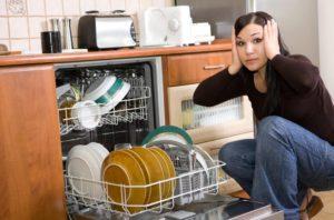 женщина держиться за голову возле посудомойки, установка посудомоечной машины