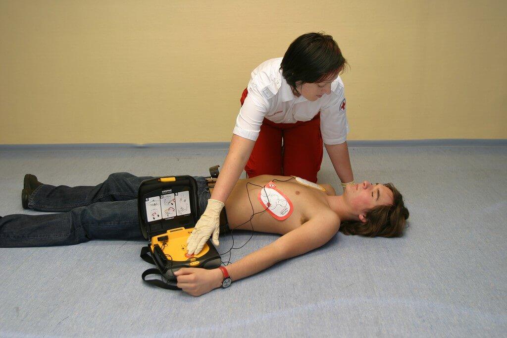 парень лежит, возле него сидит женщина, правила первой помощи при поражении электротоком