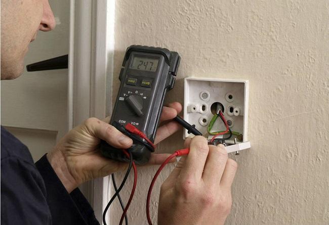 мужчина сделать прозванивает провода в розетке выключатель