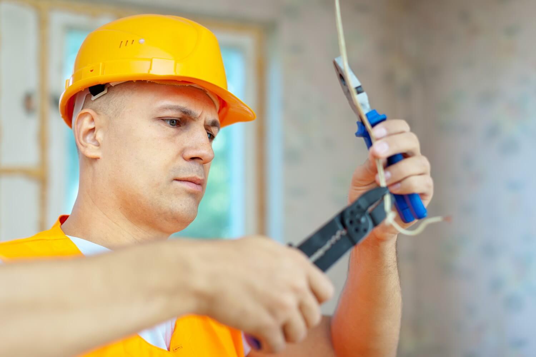 Мужчина в каске что-то делает с проводом, требования к монтажу электропроводки